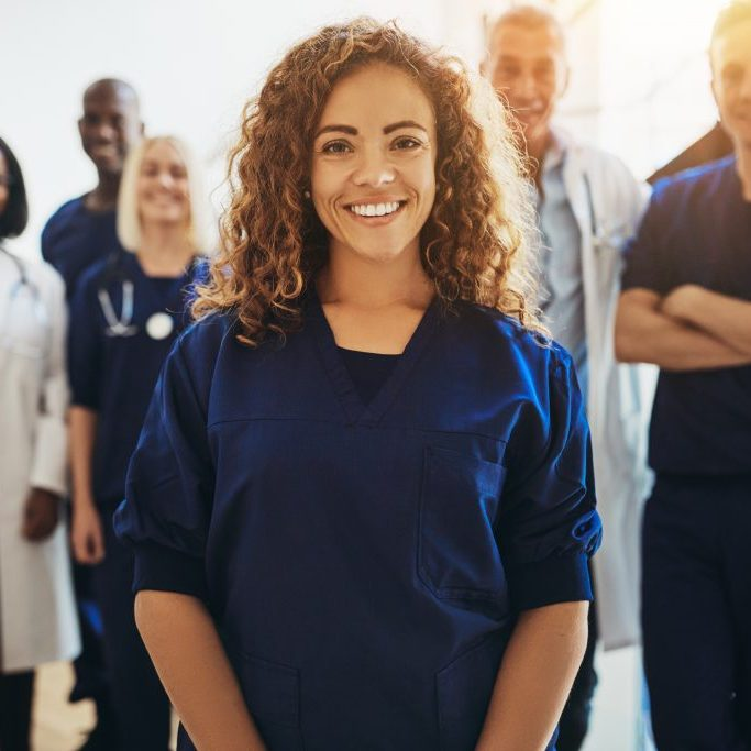 Smiling young female doctor standing in a hospital corridor with a diverse group of medical staff standing behind her